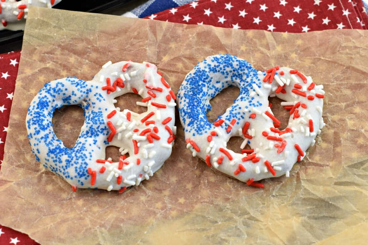 Two red white and blue white chocolate covered pretzels on a piece of parchment paper.