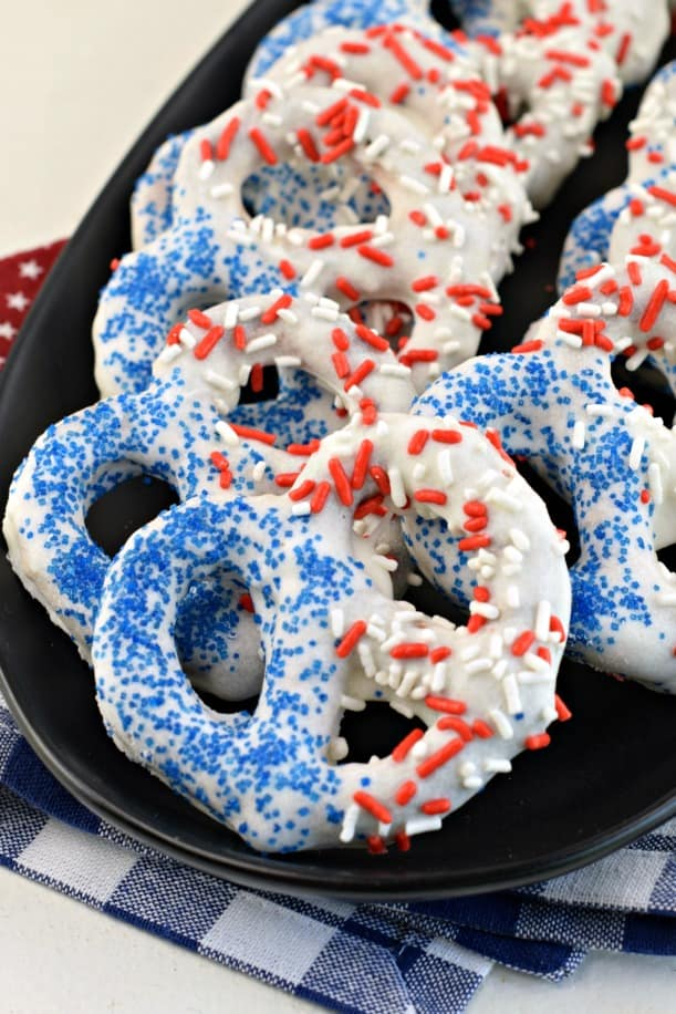 White chocolate covered pretzels with red white and blue sprinkles on a black serving plate.