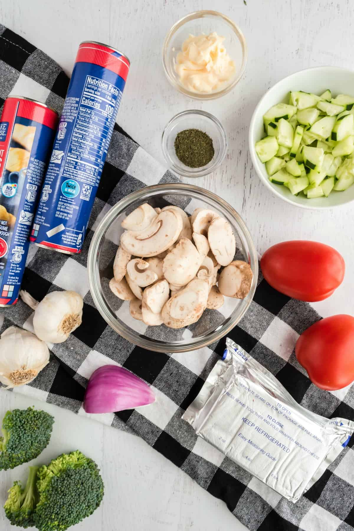 Ingredients needed for making a crescent roll pizza with vegetables.