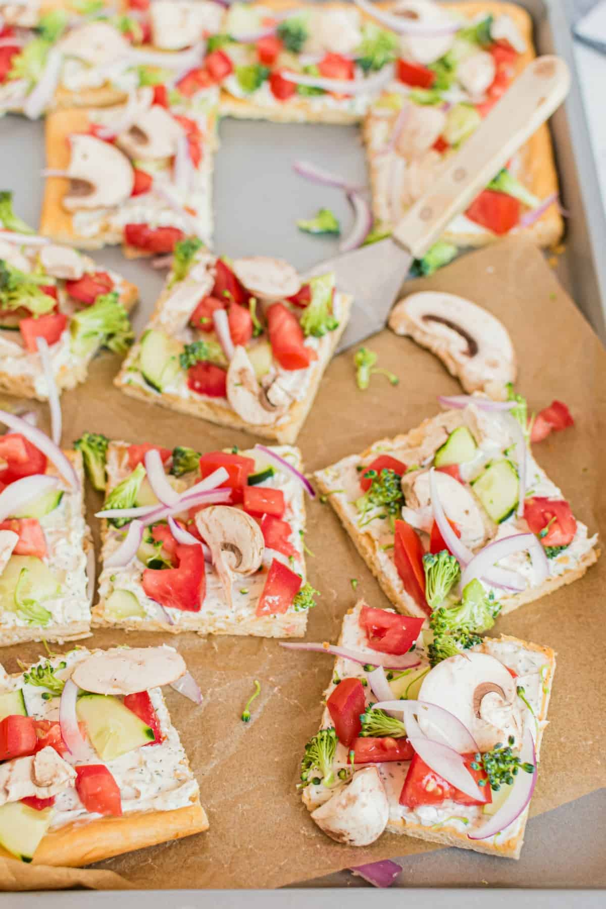 Crescent roll pizza crust topped with dill cream cheese spread and fresh veggies. Cut into squares.