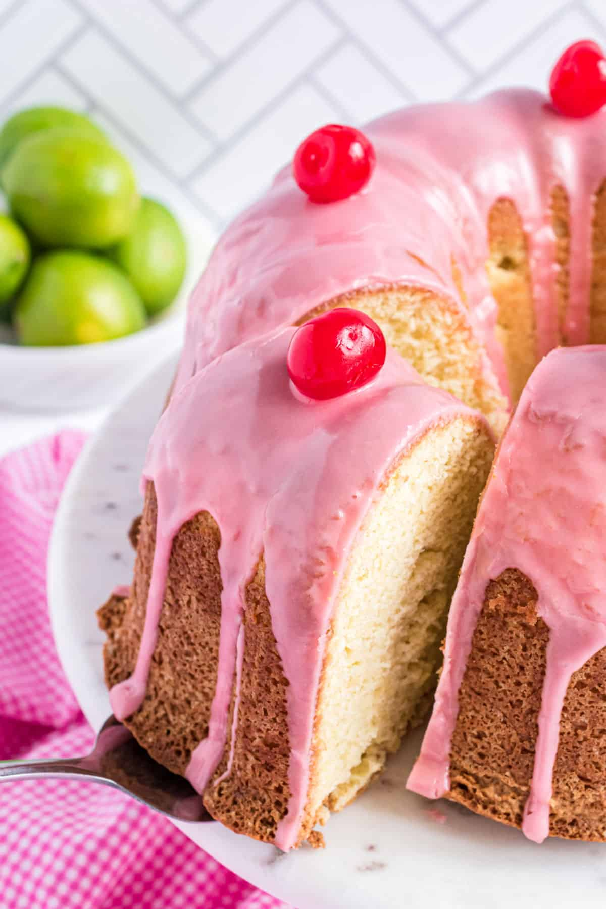 Slice of cherry pound cake being removed from plate.