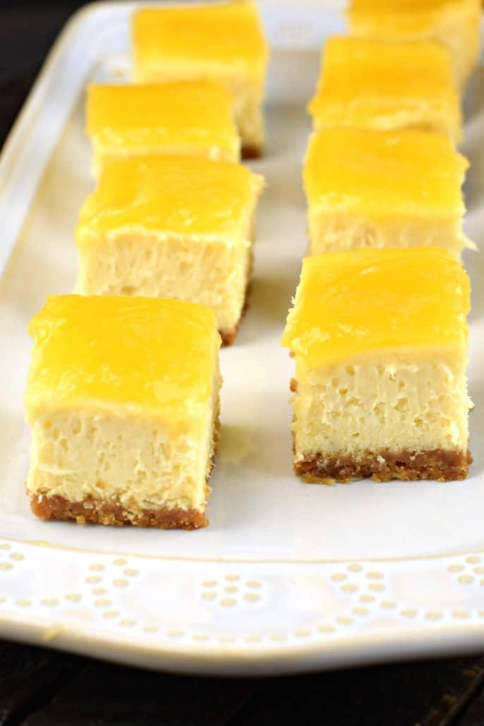 Bites of lemon cheesecake on a white plate.