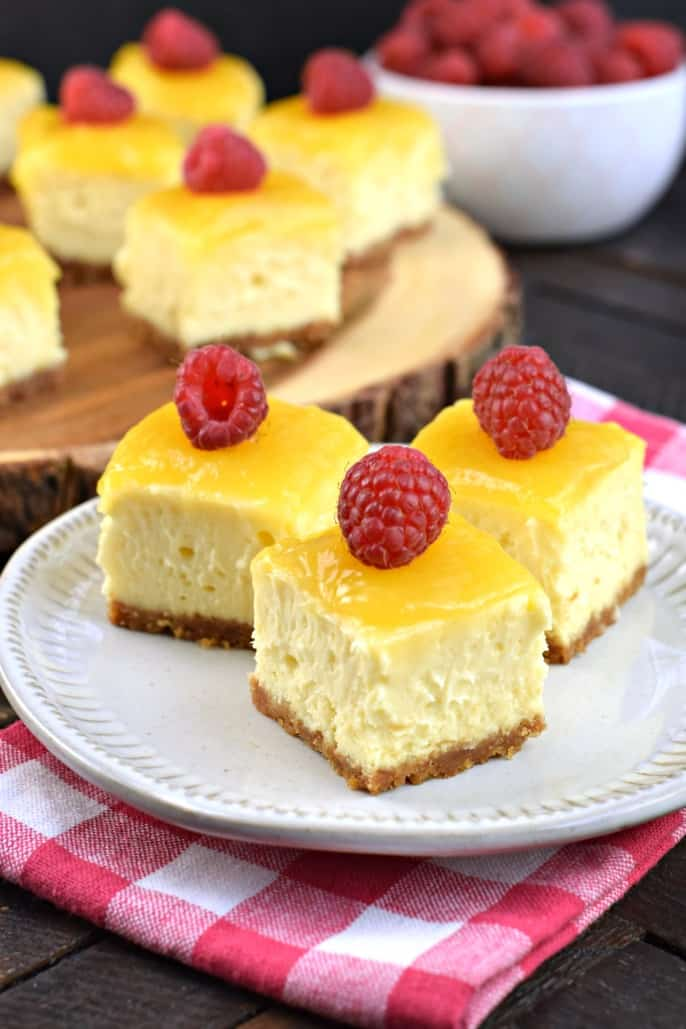 Cheesecake bites topped with lemon curd and fresh raspberries.