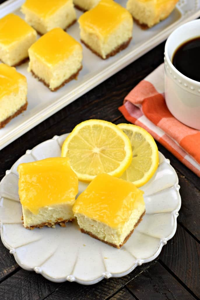 Cheesecake bites topped with lemon curd on a white plate with fresh lemon slices.