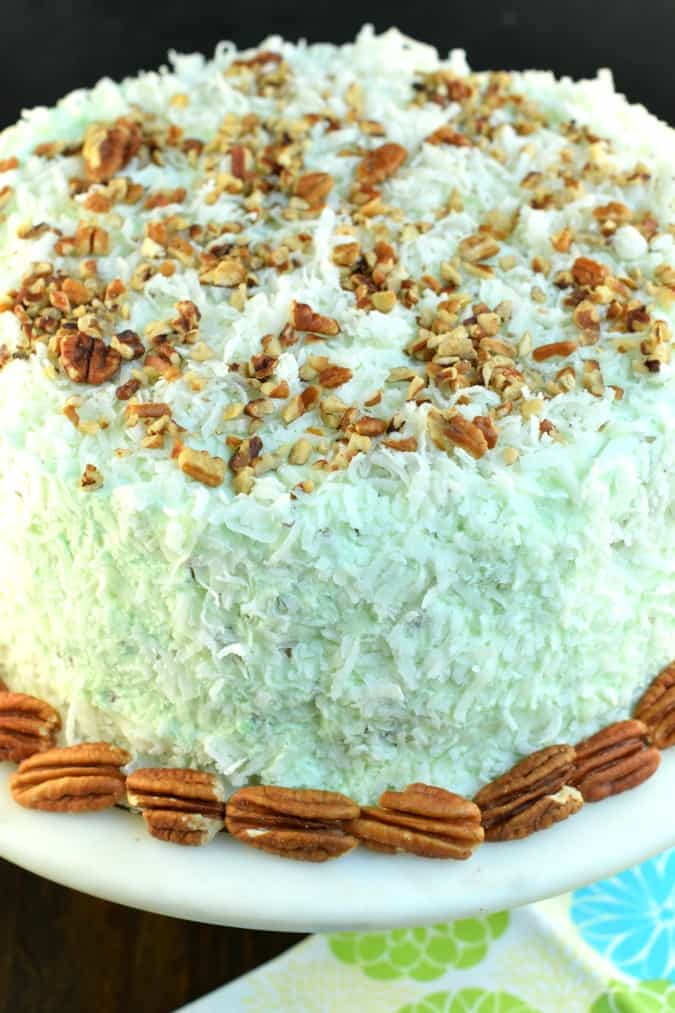 Watergate cake topped with pecans and coconut on a white cake platter.