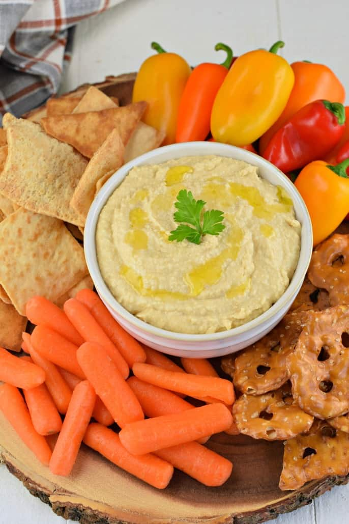 Hummus with olive oil in a white bowl and served with veggies, pretzels, and pita chips.