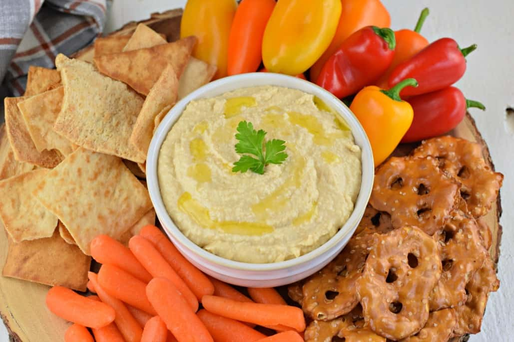 Hummus in a bowl and served on a platter with pretzels, pita chips, and vegetables.