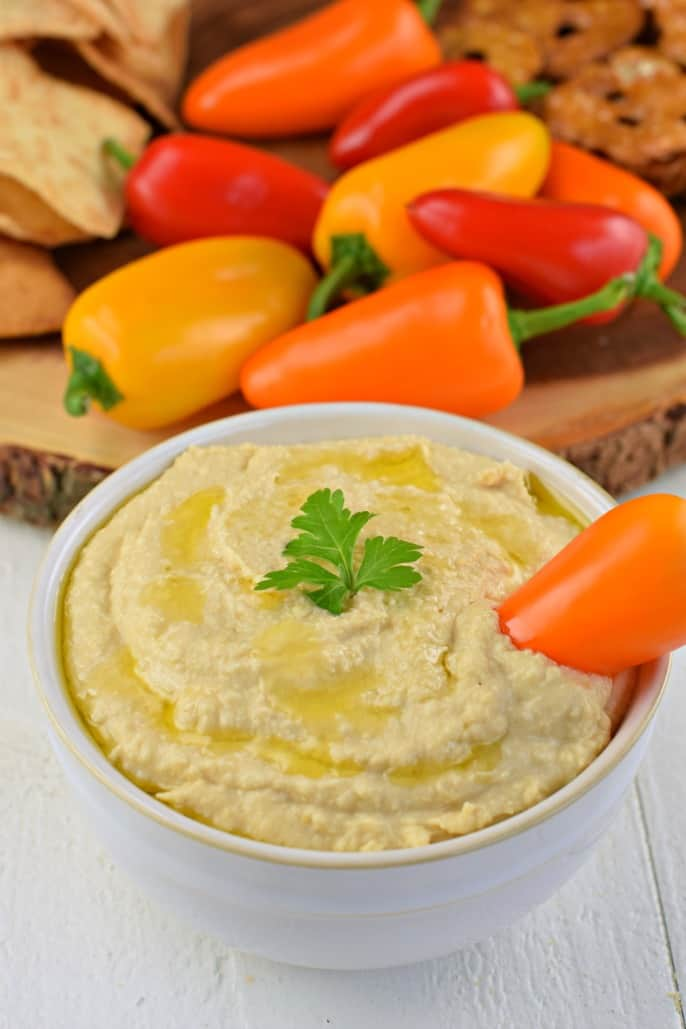Homemade hummus in a white bowl drizzled with olive oil.
