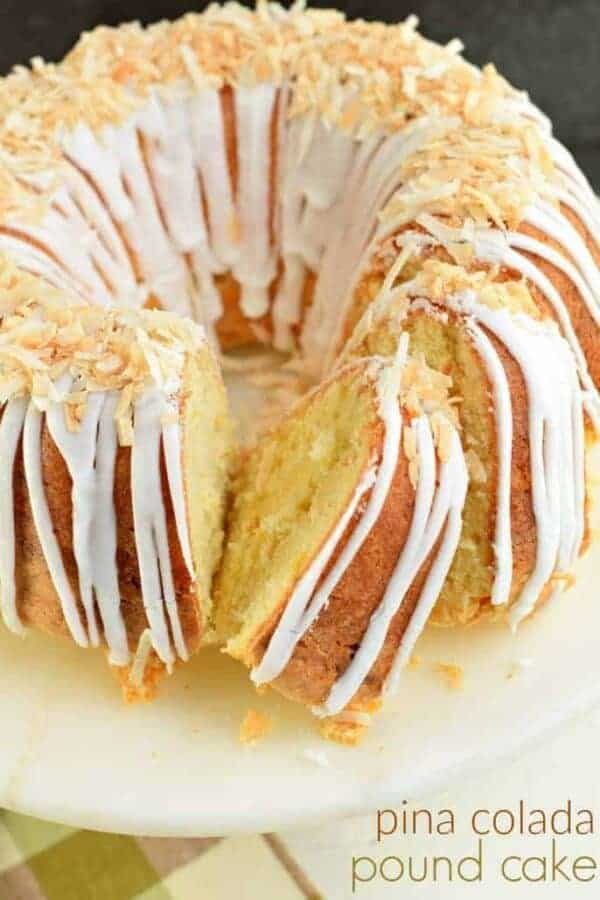 Pina colada pound cake on white cake plate with toasted coconut.