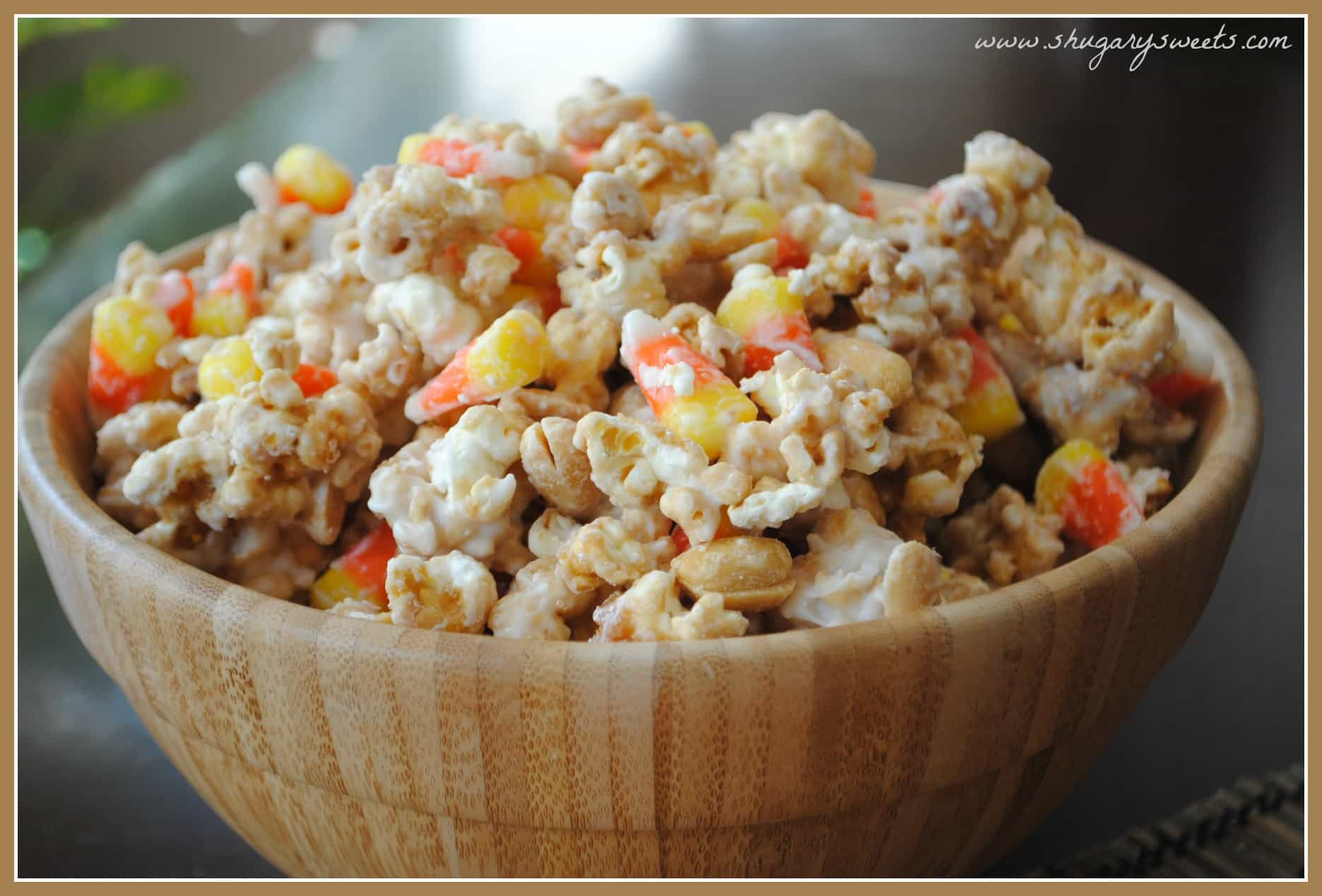 Wooden bowl filled with homemade caramel corn with peanuts and candy corn.