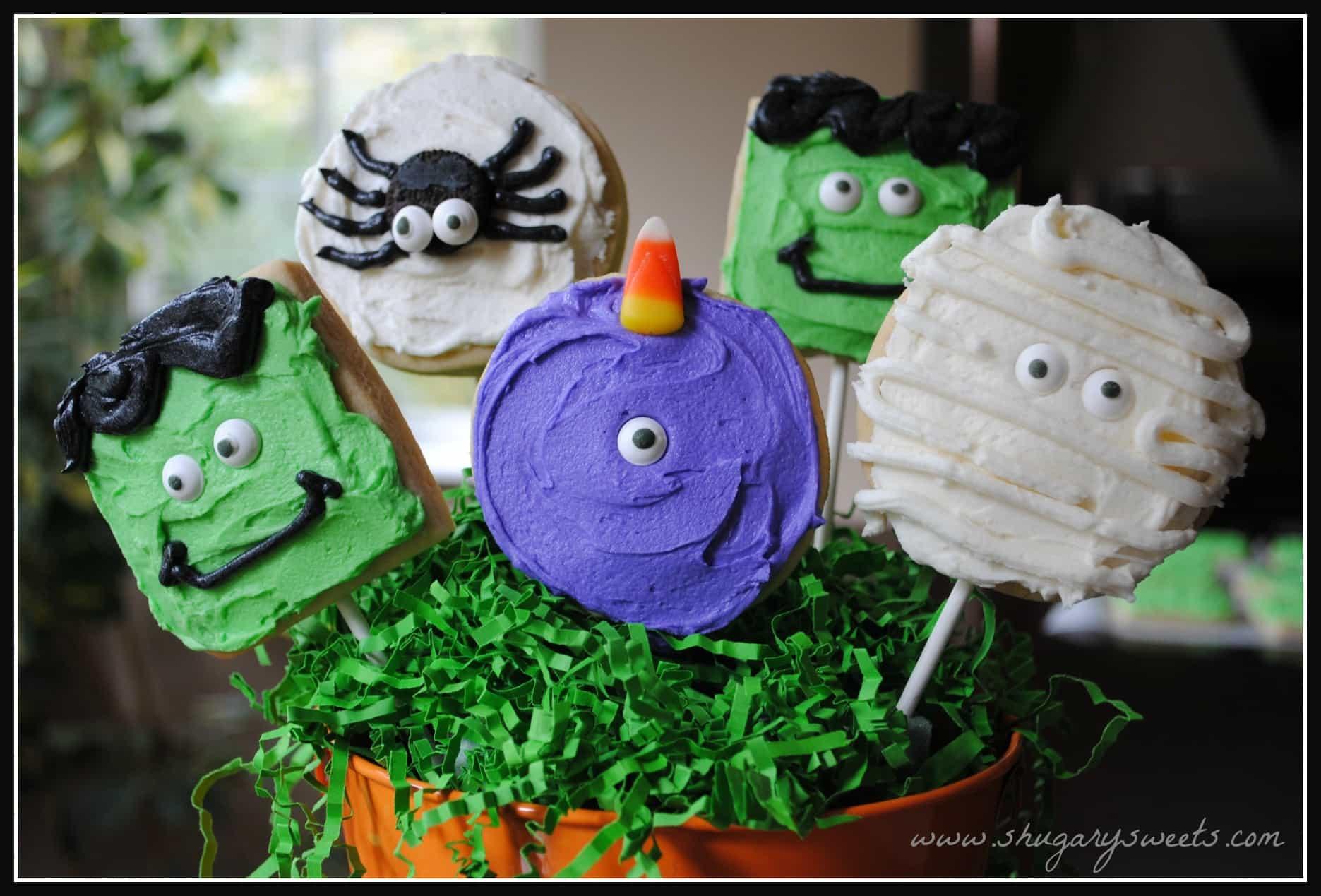 Monster shaped sugar cookies on lollipop sticks in a halloween bucket.