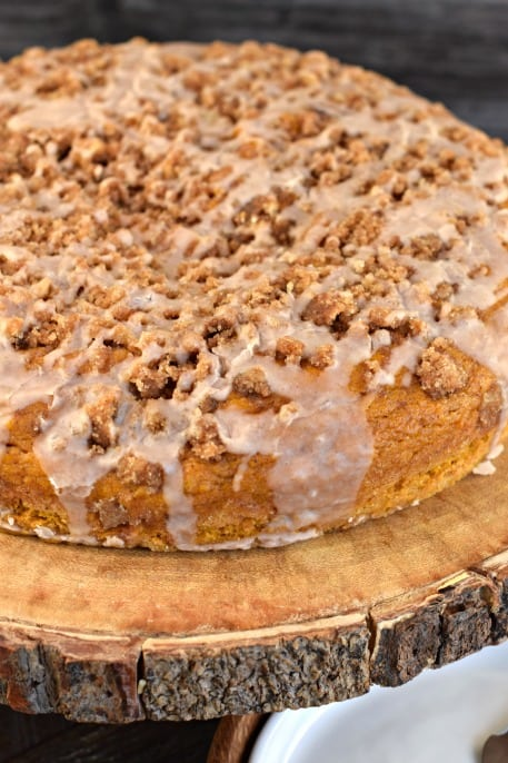 Pumpkin Coffee Cake with cinnamon struesel and vanilla glaze on wooden cake plate