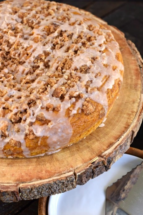 Pumpkin streusel coffee cake with glaze on a wooden cake platter.