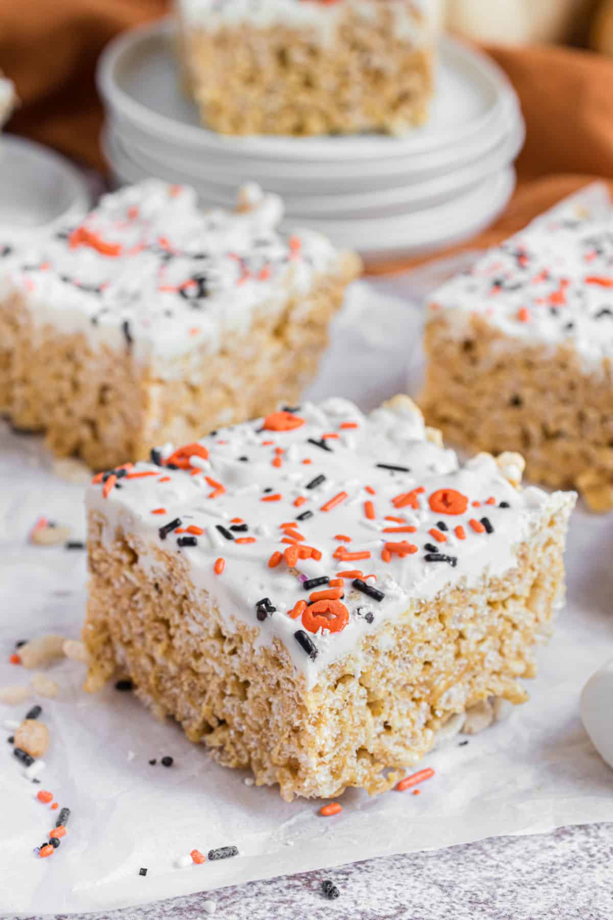 Pumpkin flavored rice krispie treats with white chocolate and sprinkles.