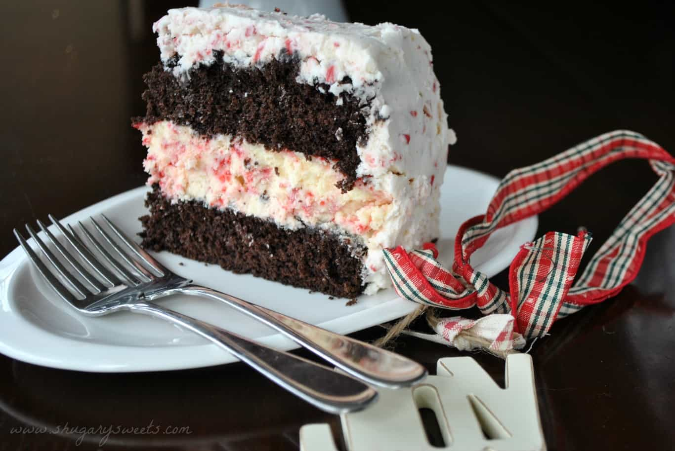 Slice of chocolate cake with peppermint cheesecake and frosting.