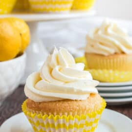 Lemon cupcake topped with lemon frosting on white plate.