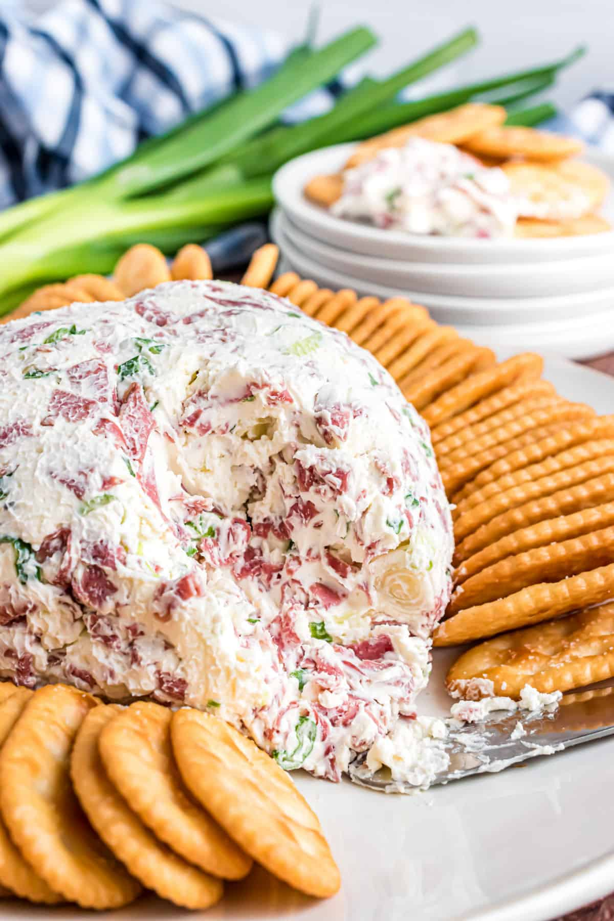 Chipped beef cheese ball with a scoop removed and served with crackers.