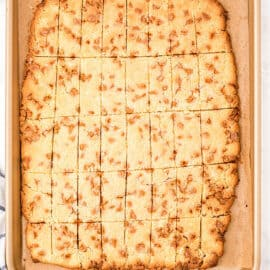 Butterscotch shortbread cookie bars on parchment paper lined baking sheet.