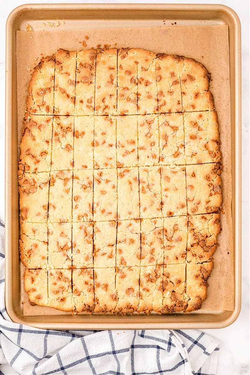 Butterscotch shortbread cookie bars on parchment paper lined baking sheet.