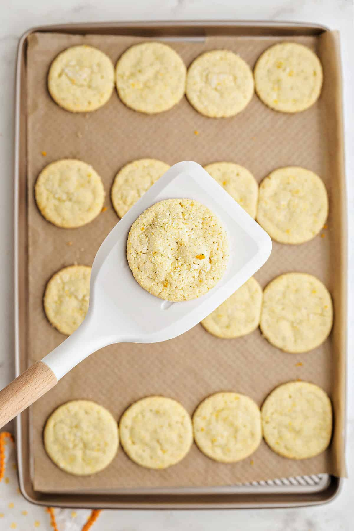 Citrus sugar cookies on cookie sheet being removed with spatula.