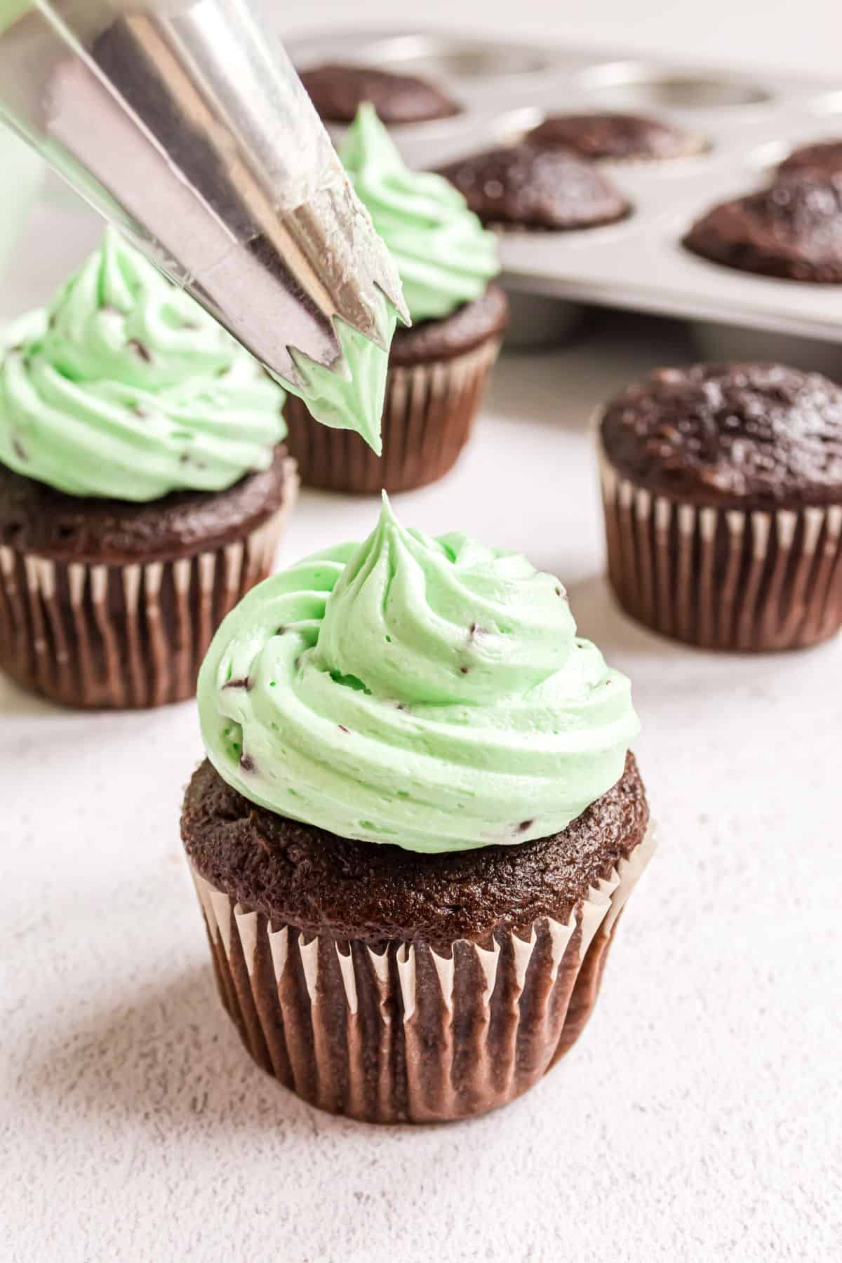 Mint chocolate chip frosting being piped onto a chocolate cupcake.