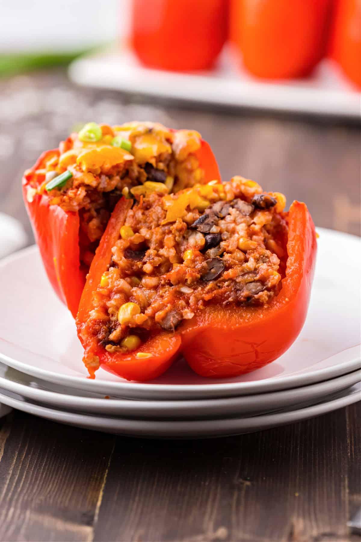 Stuffed red pepper cut in half on a plate.