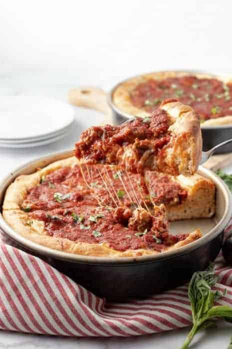 Slice of deep dish pizza being lifted out of a pan.