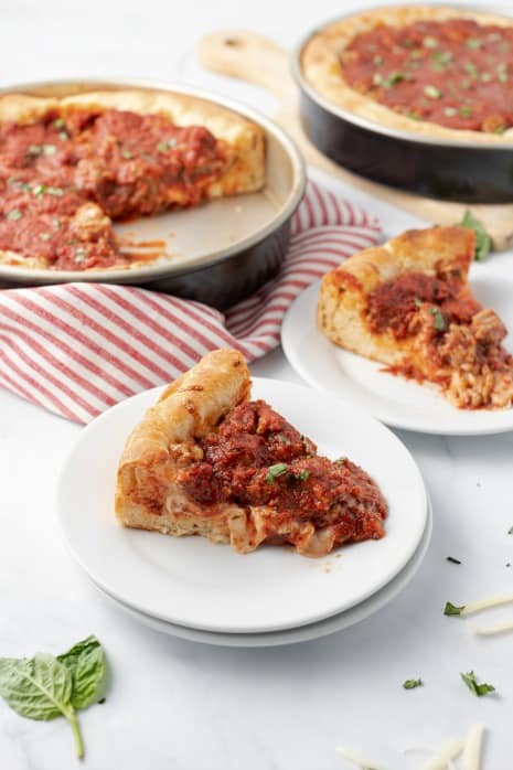 Slices of deep dish pizza on plates.