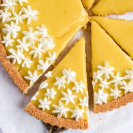 Lemon tart cut into 8 slices and topped with whipped cream.