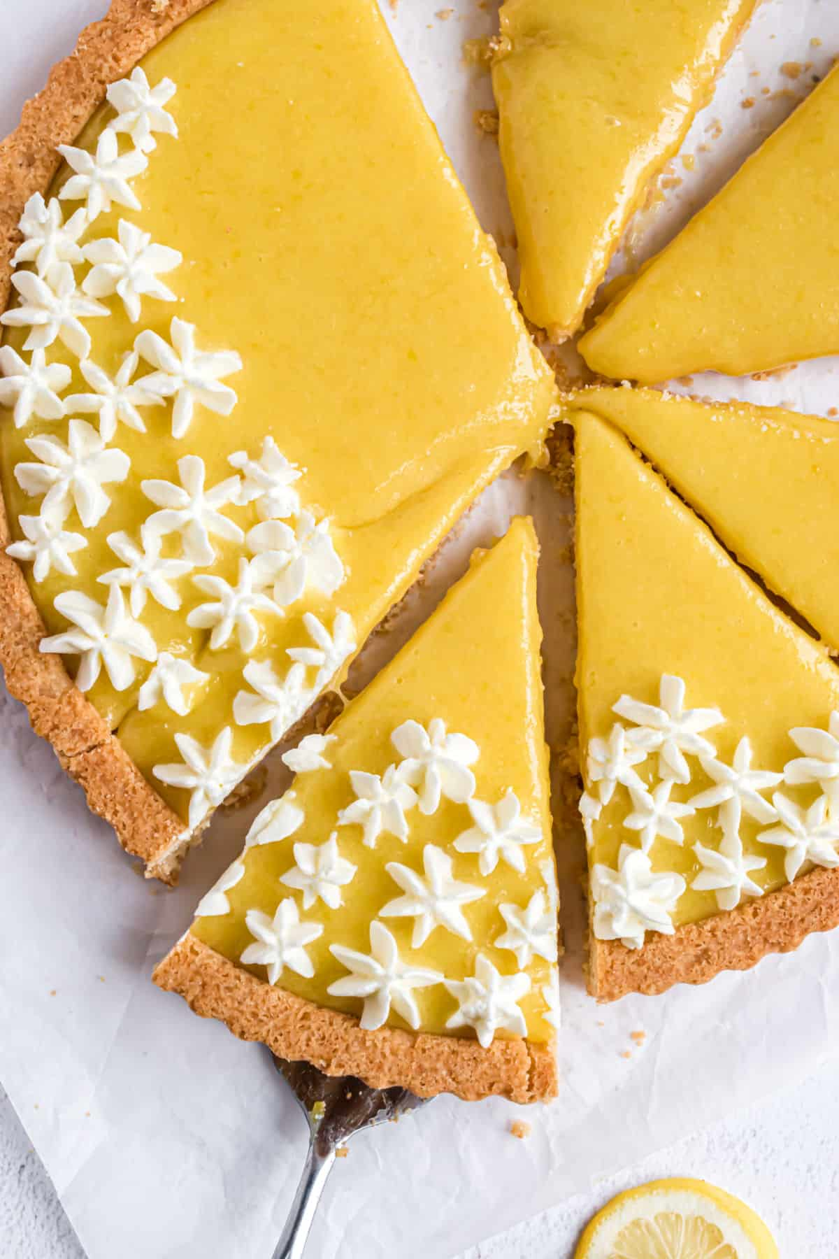 Lemon tart with whipped cream, sliced into triangles.