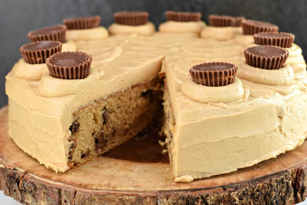Peanut butter cake with frosting and Reese's peanut butter cups on top, served on a wooden cake platter.