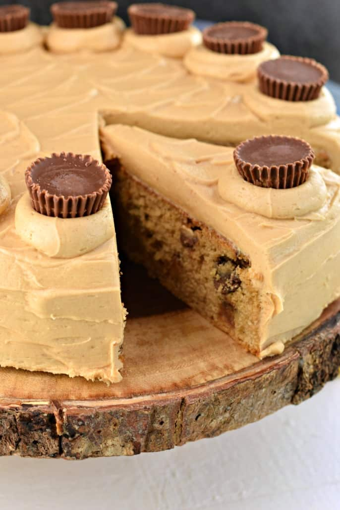 Peanut Butter cake on a wooden cake plate and topped with reese's peanut butter cups.
