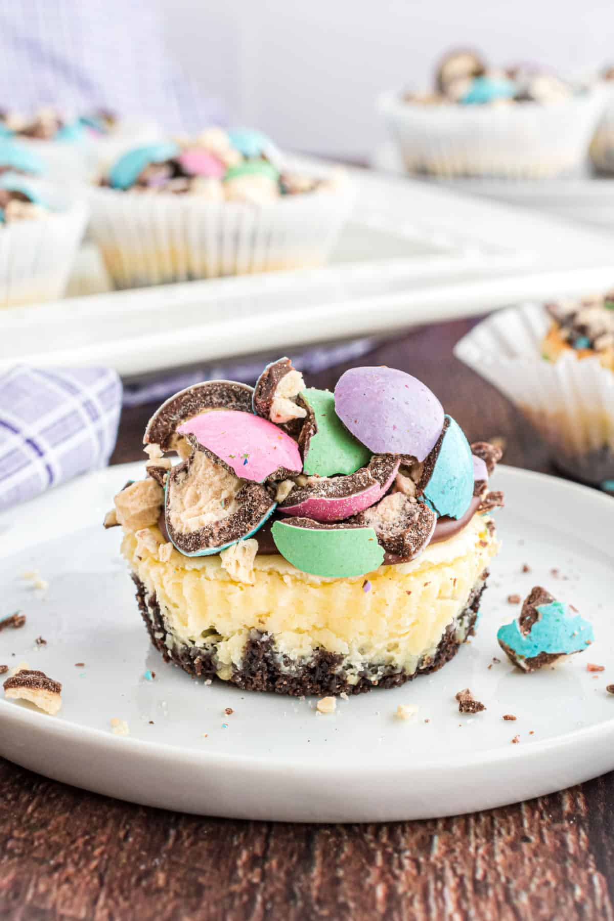 Mini cheesecakes topped with ganache and colored malt balls.