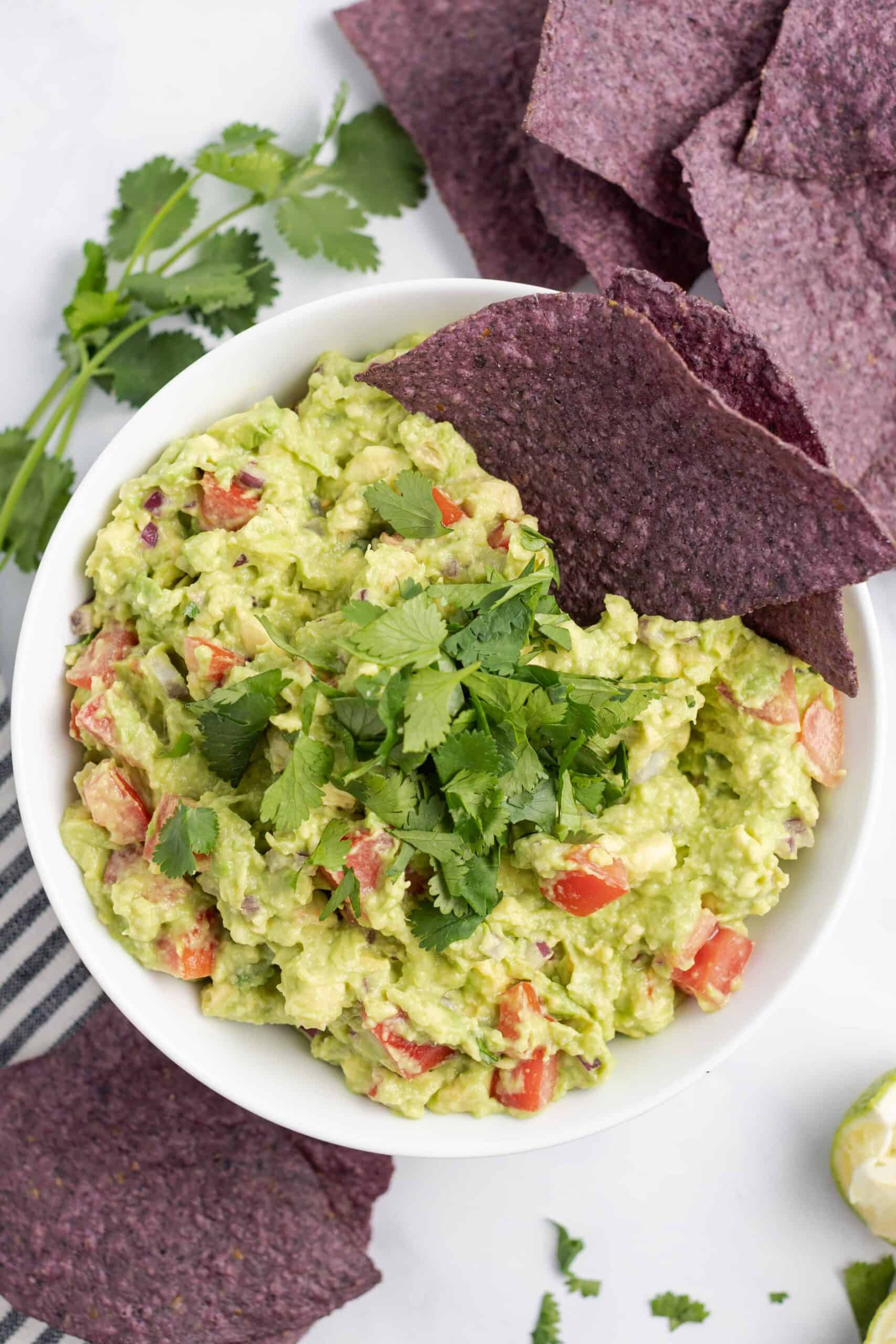 Bowl of chunky guacamole garnished with blue corn chips and cilantro