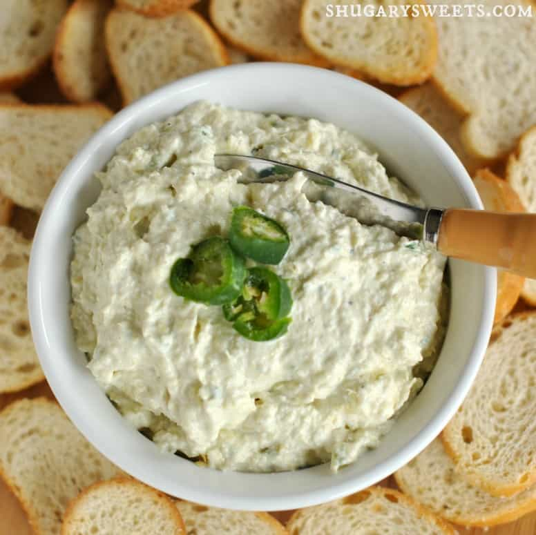 Top view of a bowl filled with artichoke jalapeno dip and surrounded with slices of french bread.