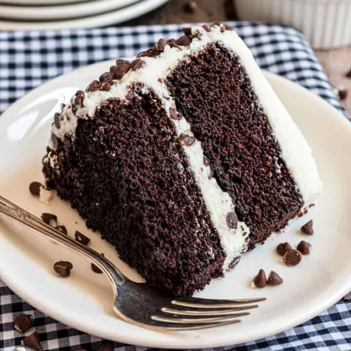 Slice of double layer chocolate cake with vanilla frosting on white plate with fork.