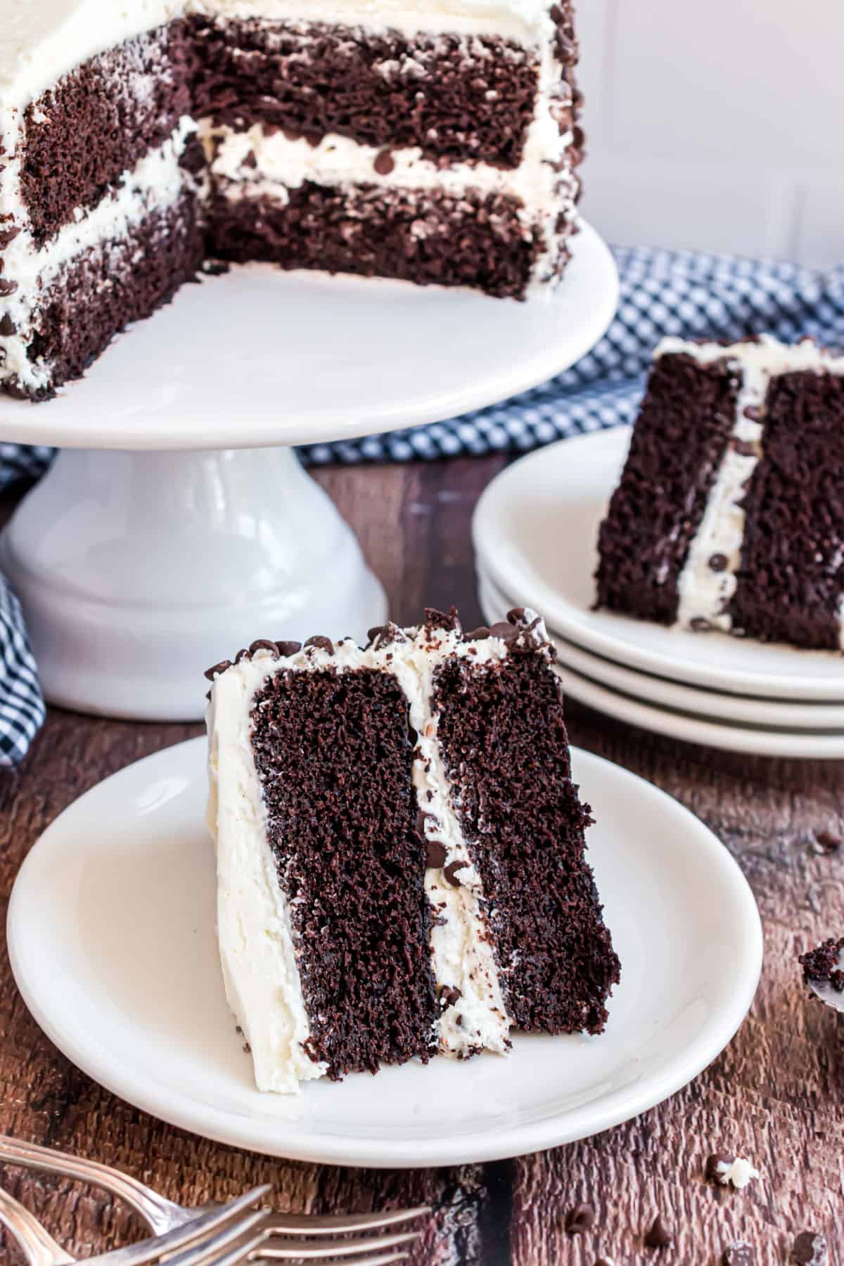 Dark chocolate cake slices on white plate and topped with vanilla frosting.