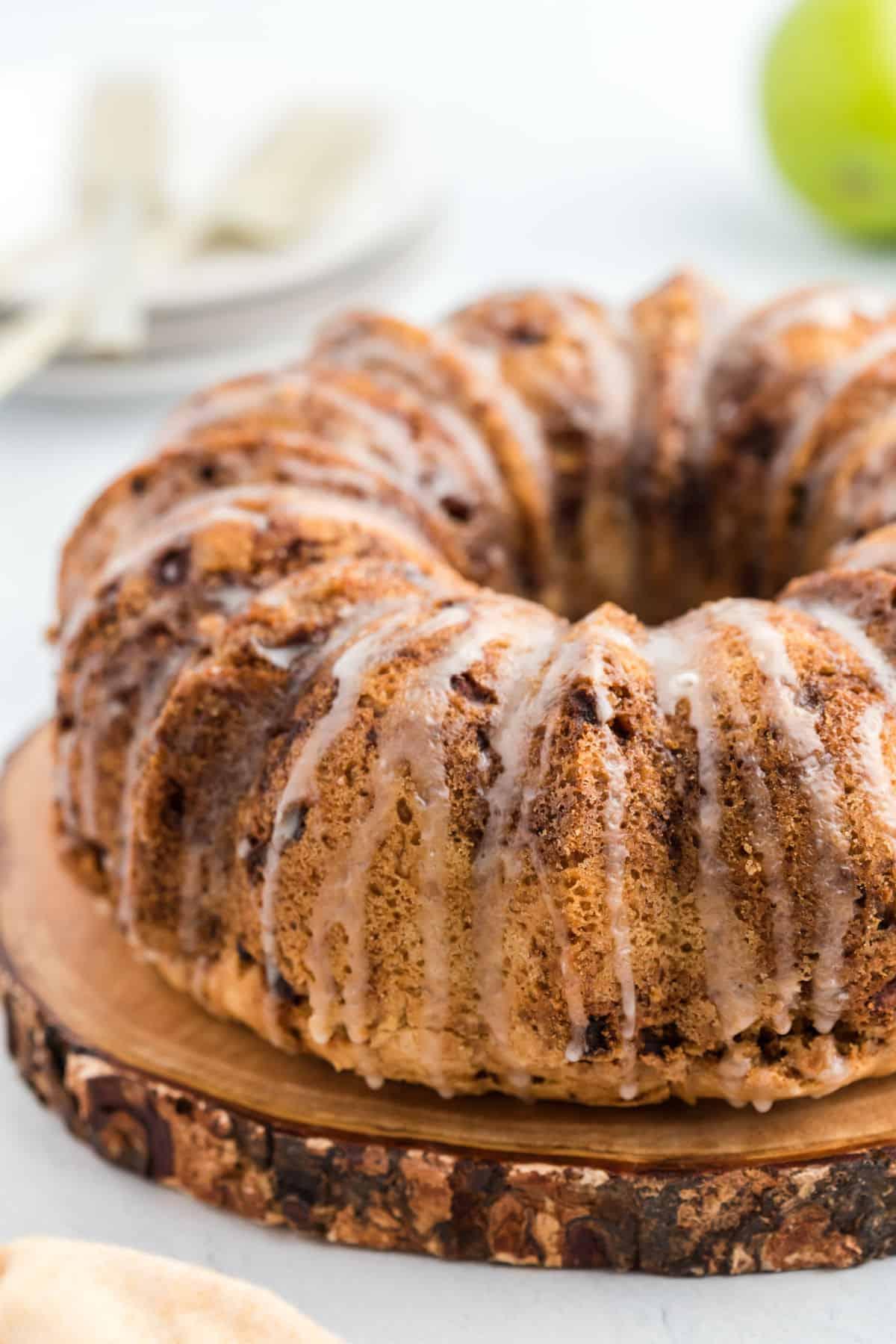 Apple bundt cake on wooden serving plate with a glaze.