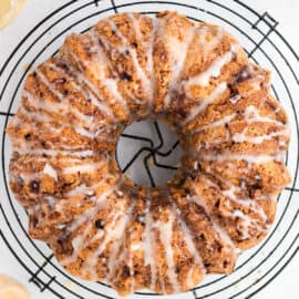 Apple bundt cake drizzled with honey icing on a wire cooling rack.