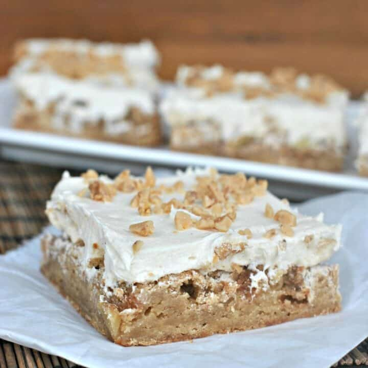 Apple blondies with caramel buttercream, on a piece of parchment paper.
