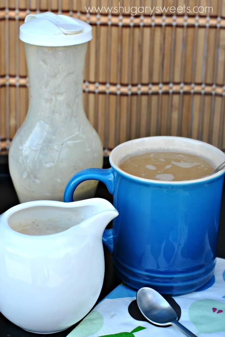 Creamer, mug of coffee, and shaker of coffee creamer on table.