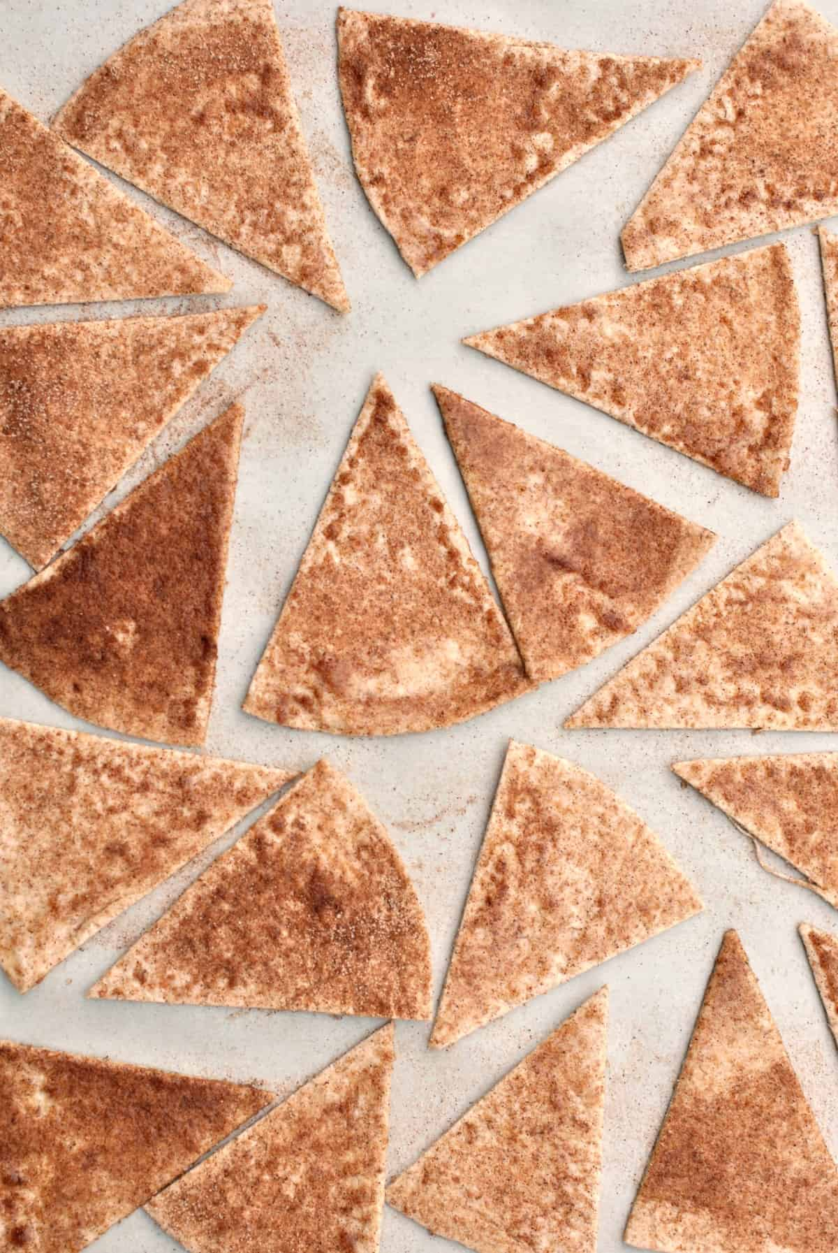 Cinnamon sugar tortilla chips on a baking sheet.