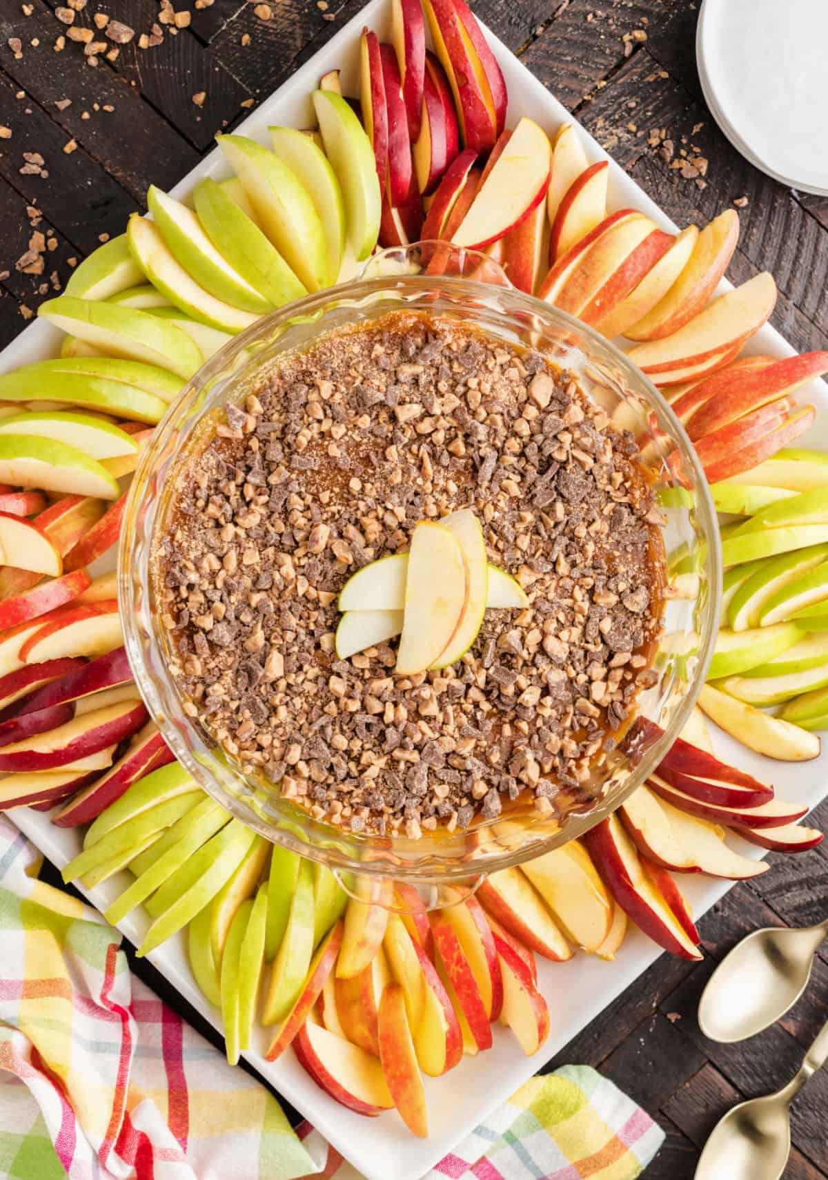 Caramel apple dip in pie plate with sliced apples for serving.