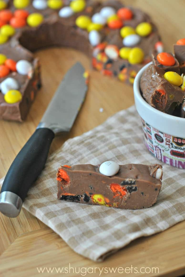 Slice of halloween fudge with oreos, candy corn, and m&m's.