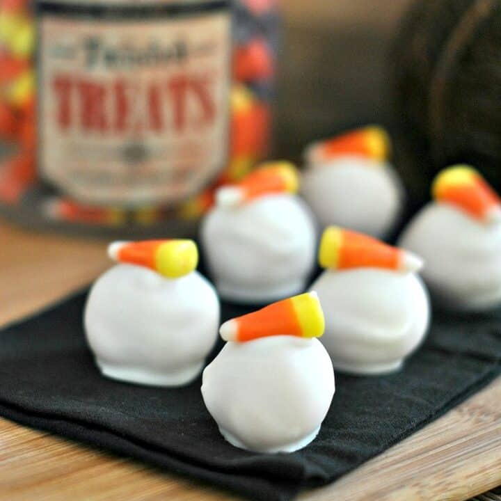 Oreo balls dipped in white chocolate and topped with a piece of candy corn.
