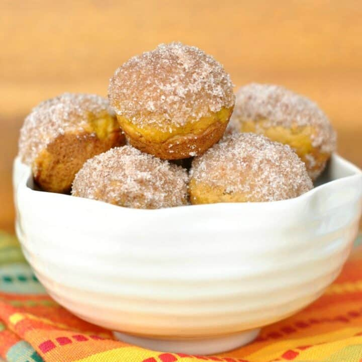 Bite sized Pumpkin Donut Muffins! Roll your baked donuts in butter and cinnamon sugar for a bite sized breakfast treat no one can resist.