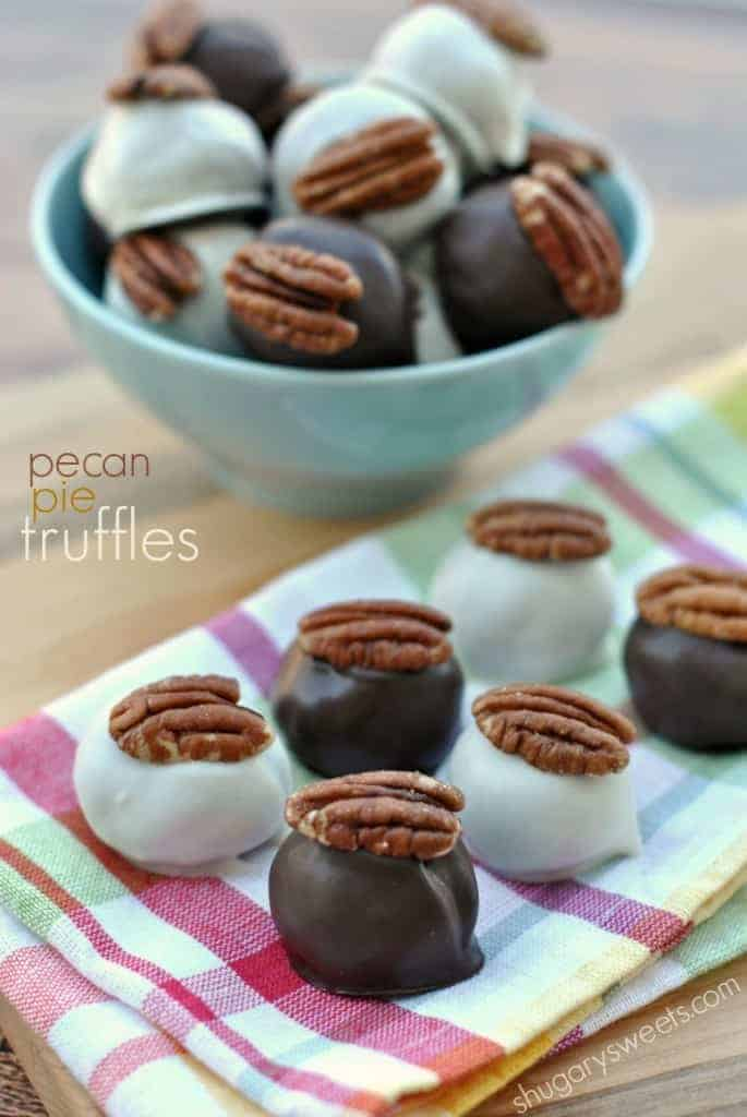 Pecan pie truffles on colorful napkin topped with a pecan halve.