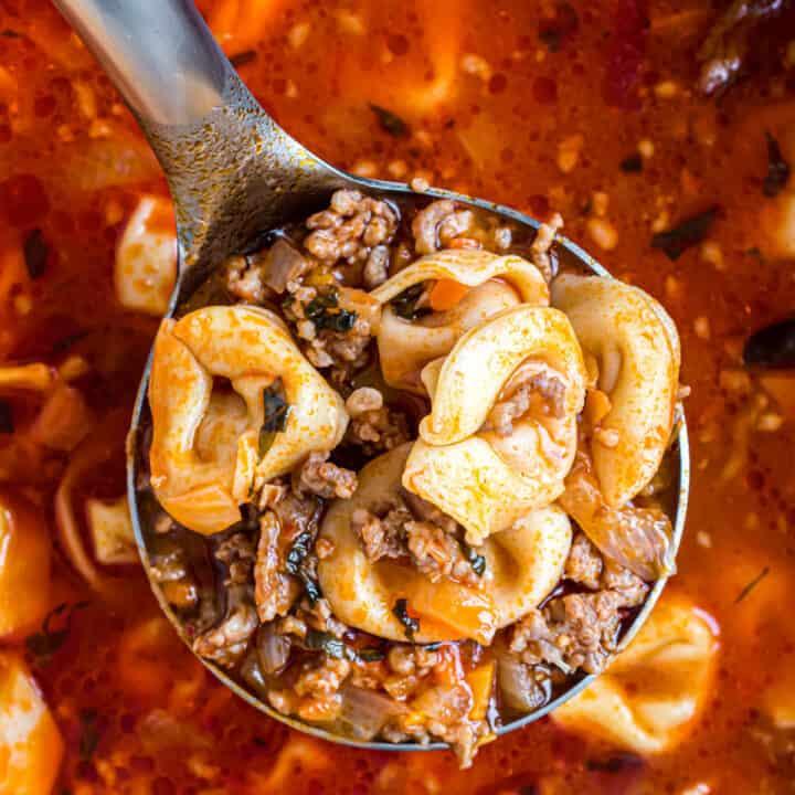 Sausage tortellini soup on a ladle.