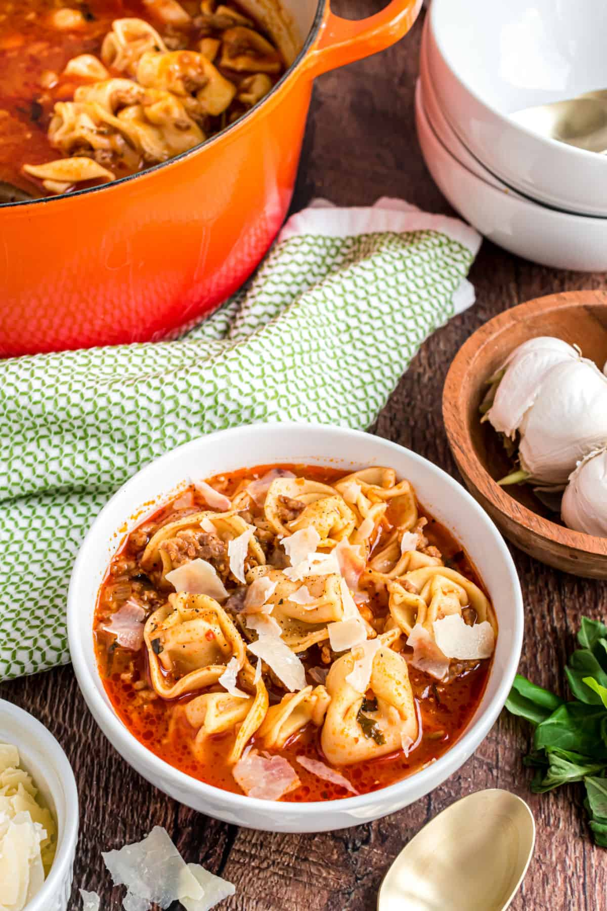 Sausage tortellini soup in a white bowl with shaved parmesan cheese.