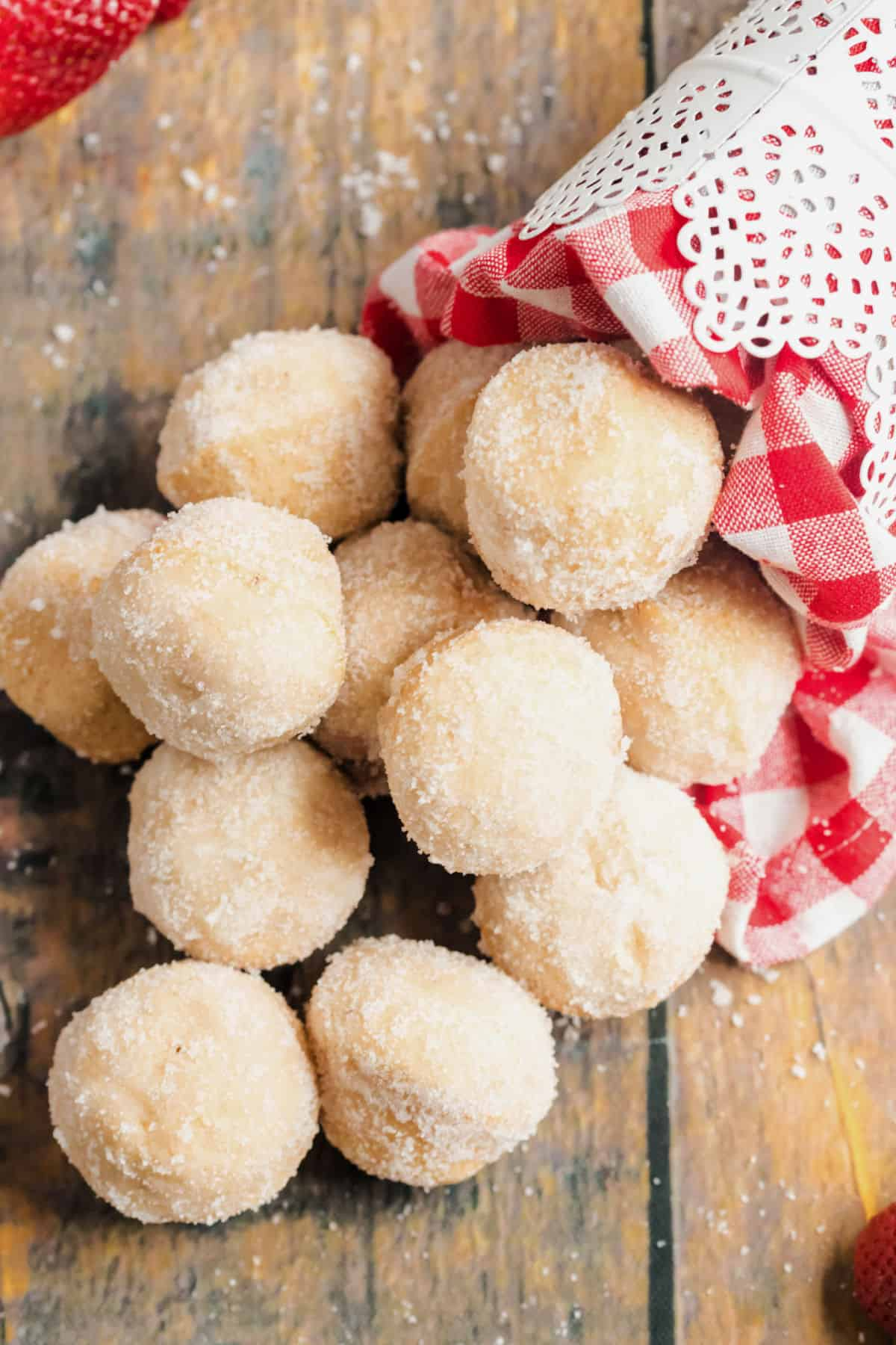 Jelly filled donut holes falling out of a bowl.